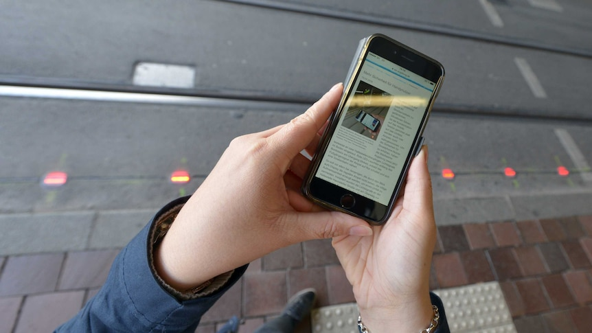 A line of lights embedded in the pavement can be seen past a hand using a mobile phone.