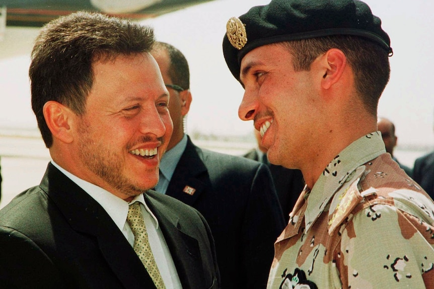 A file photo shows Jordan's King Abdullah II laughing with his younger half brother Prince Hamza.