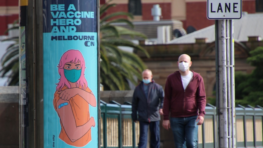 Two men walk across a Melbourne CBD bridge with a COVID vaccination poster in view