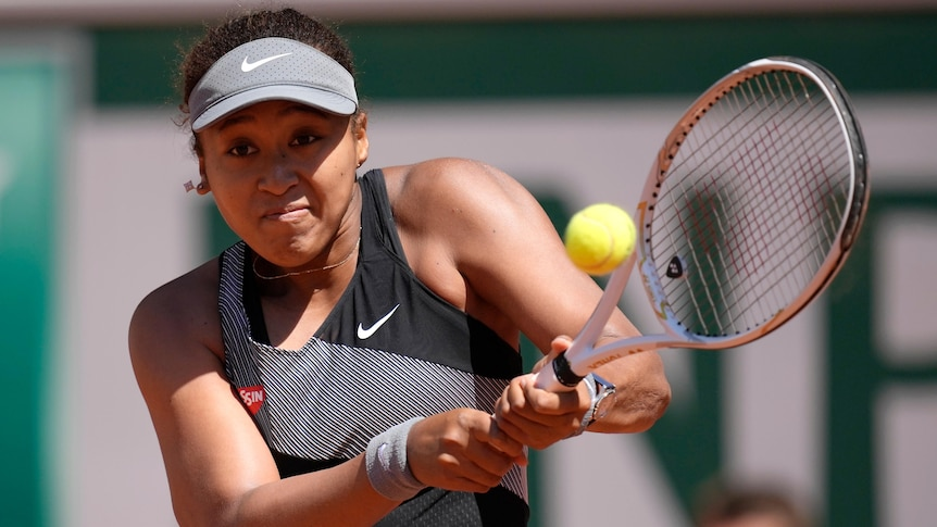 A Japanese tennis player hits a double-fisted backhand at the French Open.