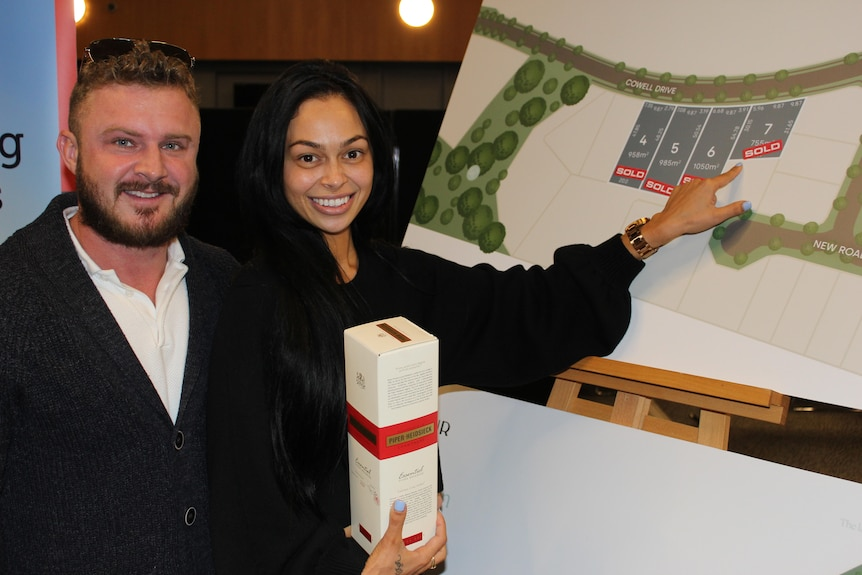 Couple holding champagne pointing to a poster with housing development layout