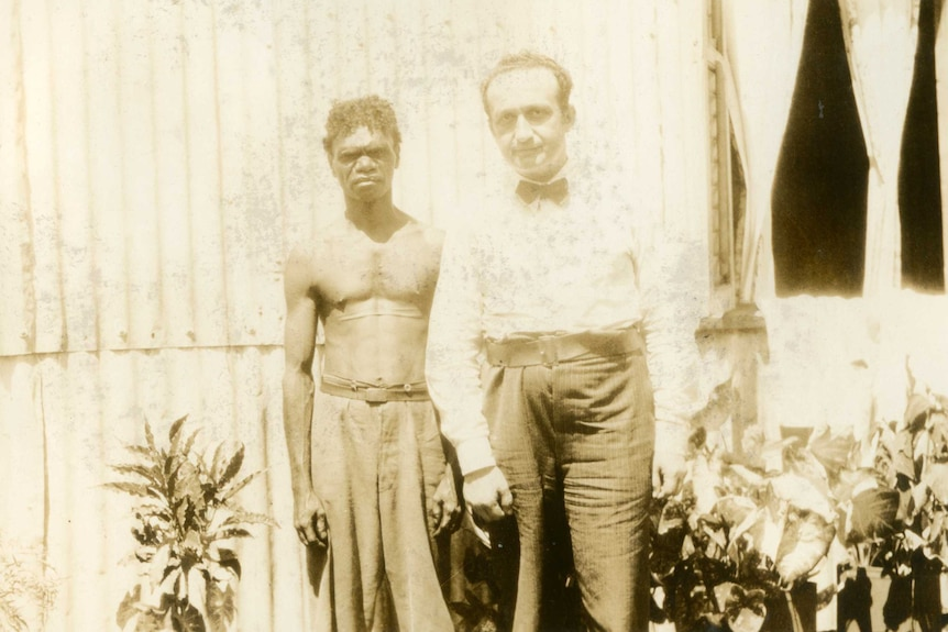 A shirtless aboriginal man who has two long scars on his chest stands next to a white man wearing a bow tie.