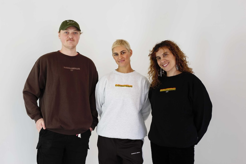 Three people from Clothing The Gap with the new rebranded jumpers saying 'Clothing The Gaps' with an added 's'.