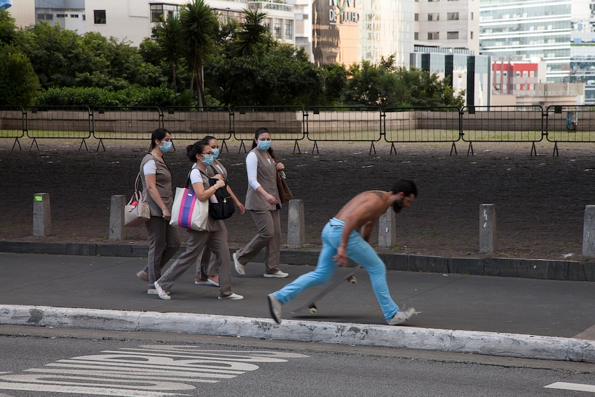 A group of women in face masks walk down a street while a man skateboards past them