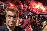 A journalist stands in front of a crowd of soccer fans holding red ad white flags. Flares go off in the distance.