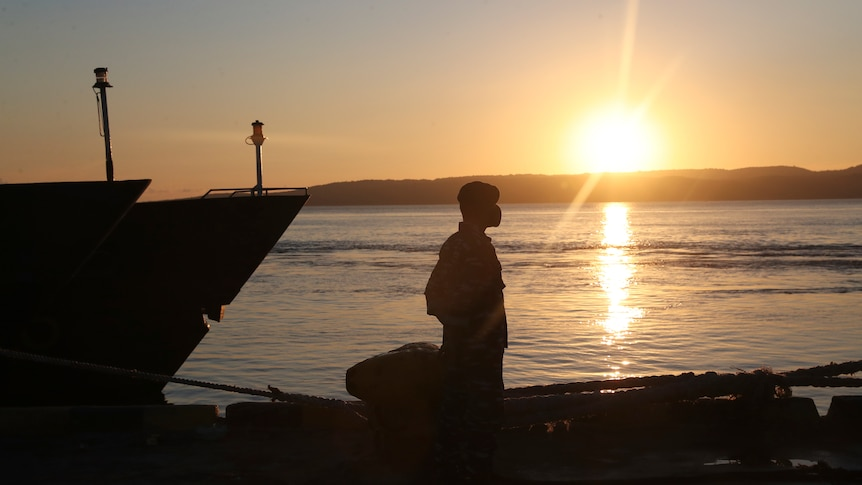 A man standing  by a boat silhouetted by a setting sun