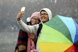 A couple takes a selfie with a mobile phone during a visit to the West Lake amid snowfall in Hangzhou.