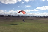 A skydiver with a red parachute lands on grass.