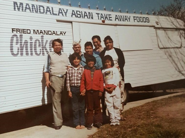A family stands smiling in front of a white bus selling takeaway Asian food. It is an old photo from decades ago.