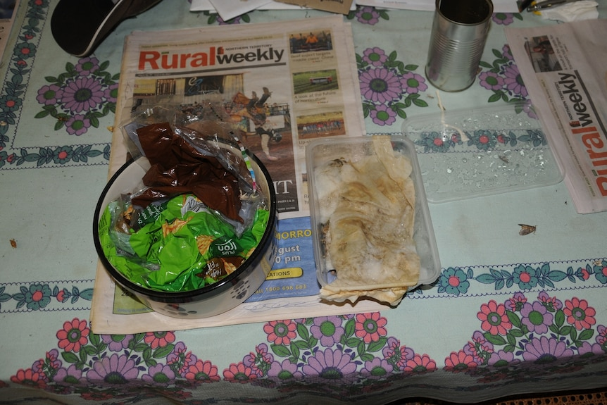 A bowl full of plastic bags and a takeaway container with dim sims on a copy of Rural Weekly.