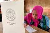 A bright wood-panelled schoolroom is turned into a polling station, with a voter in a bright pink hijab writing on polling paper