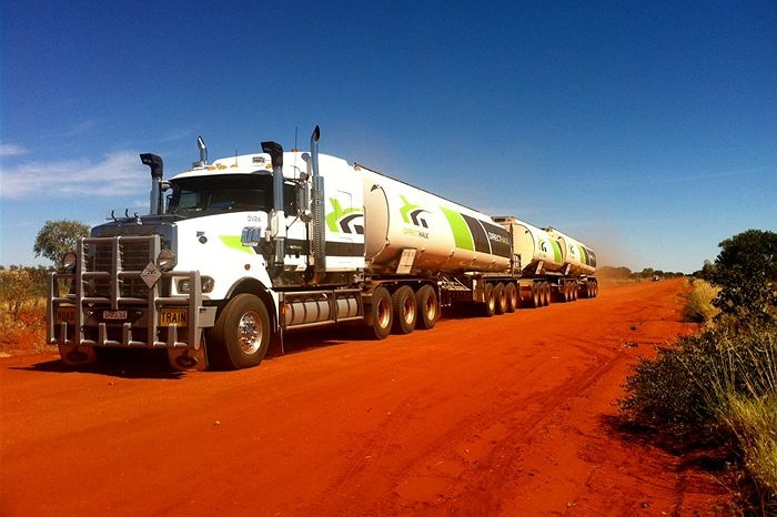 A large white truck with three trailers on a red dirt road under clear blue skies