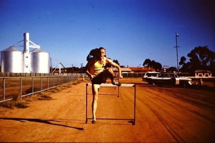 Colour photo of a man hurdling on a dirt track in a country town. There are silos in the background