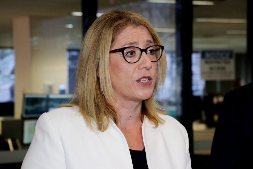 A woman with blonde hair wearing black-rimmed glasses and a white blazer.