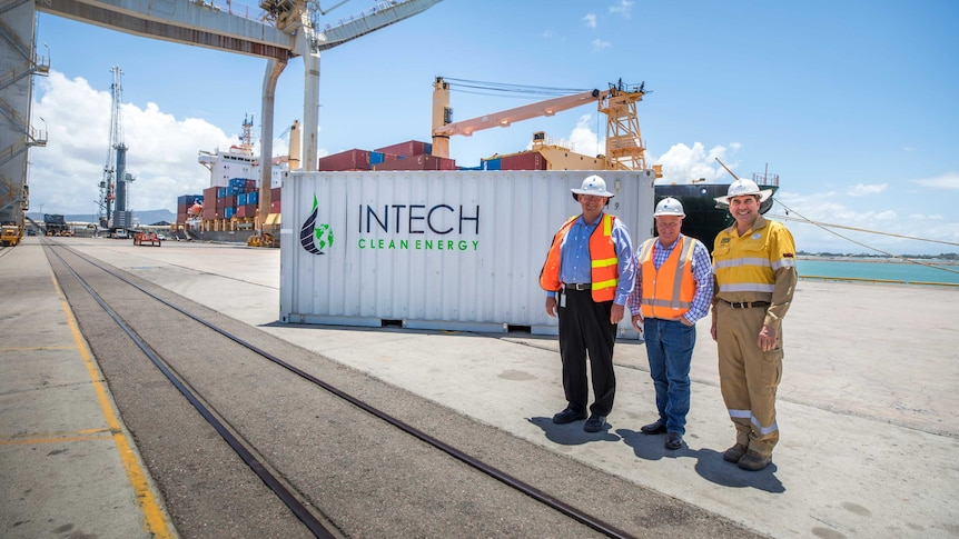 Three men wearing high vis and hard hats stand in front of a shipping container at a port