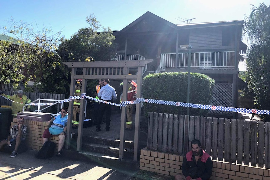 Police and residents outside a unit block where fire claimed a man's life