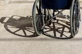 A wheelchair casts a shadow on a tiled floor.