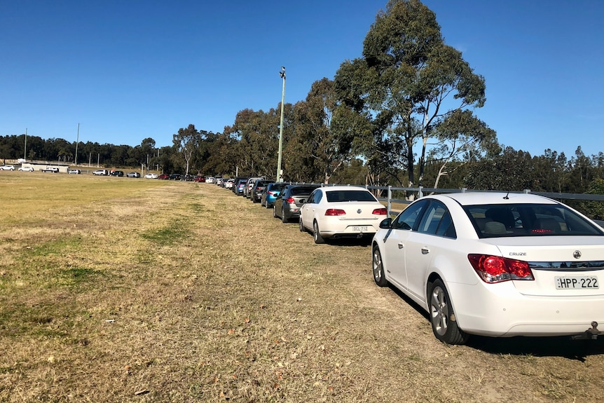 Cars line up at a showground for COVID test.