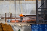 A lone construction worker wearing high-vis.
