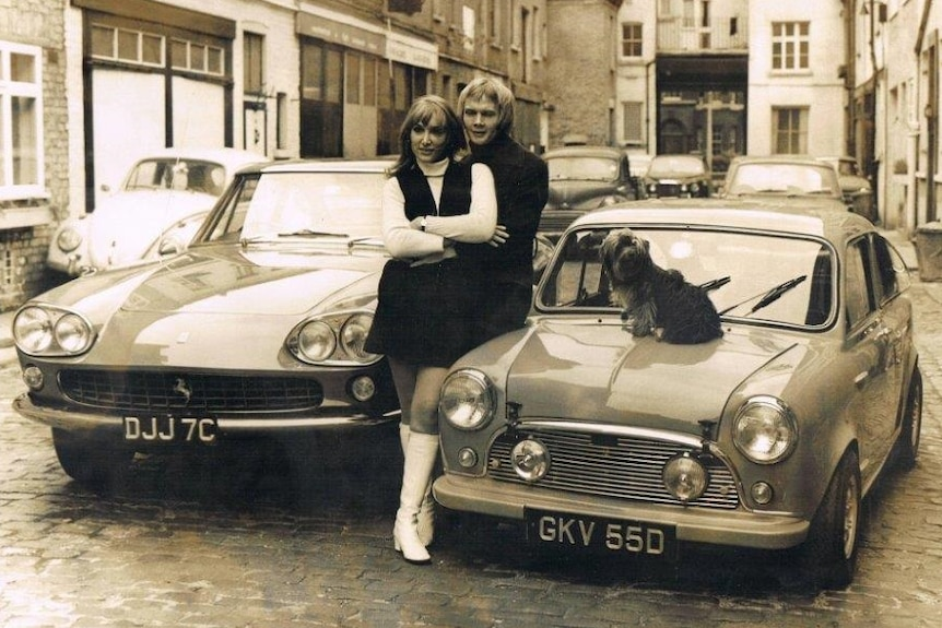 A man and woman stand next to two cars in a London Street in the sixties