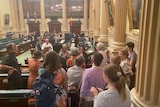 A group of people embrace in the State Parliament building.