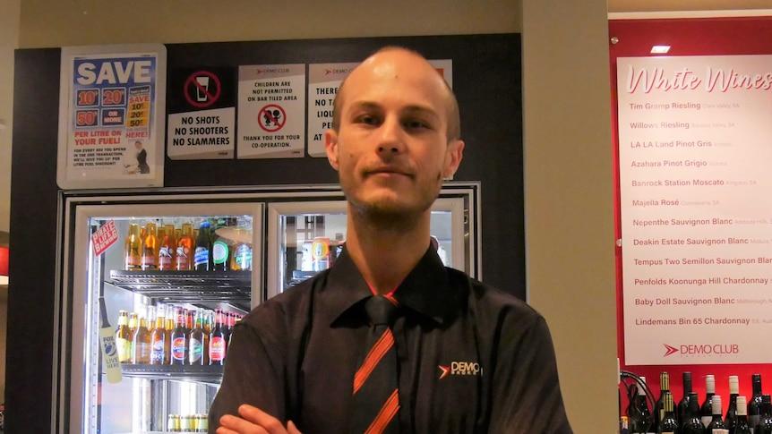 Demo Club Bar Supervisor Joshua Tracey stands cross-armed behind the club's main bar