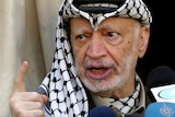 Palestinian leader Yasser Arafat talks to the press outside his office in the West Bank city of Ramallah.