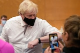 Boris Johnson wearing a black mask and a white shirt and tie elbow bumps a person at a vaccination centre as someone films