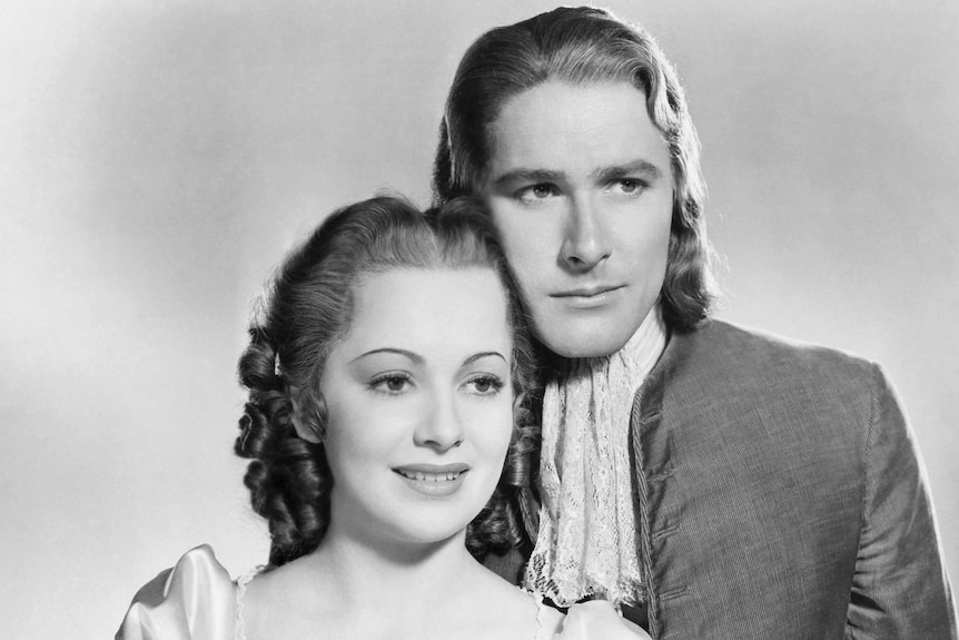 A black and white photograph shows two actors in costume posing