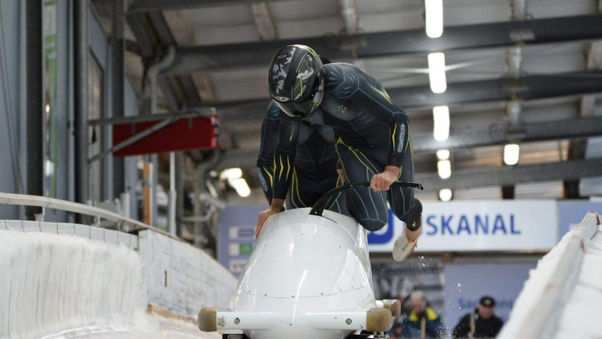 Two riders jump into bobsleigh wearing lycra speed suits