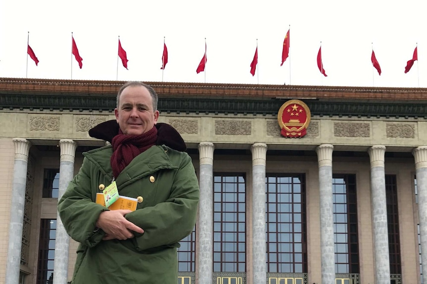 A man in a green jacket stands outside a building with columns and red flags on the top and a red and gold emblem