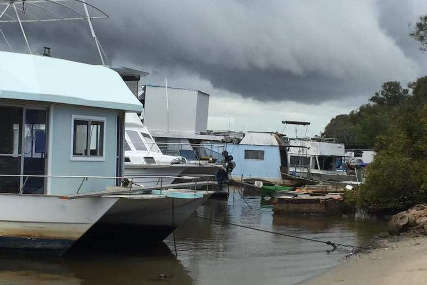 A group of ageing boats, including houseboats, anchored close to a small beach under threatening storm clouds
