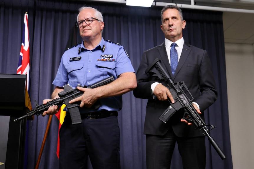 Chris Dawson and Paul Papalia standing next to each other holding guns—one is real and one is a gel blaster