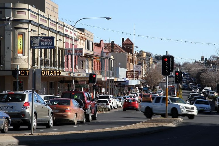 A country town street with traffic lights, cars and buildings.