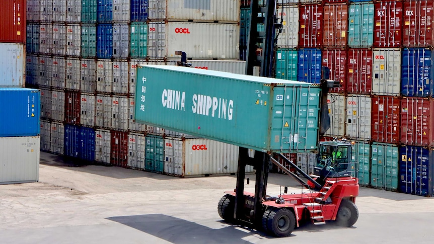 A forklift moves a China Shipping container at Port Botany, in front of a large stack of other containers.