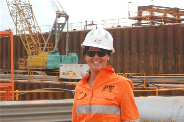 Jenny on a work site wearing an orange uniform and hard hat
