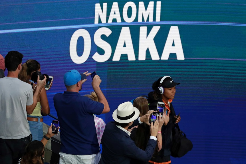 A tennis player walks onto court wearing headphones as fans take photos of her.