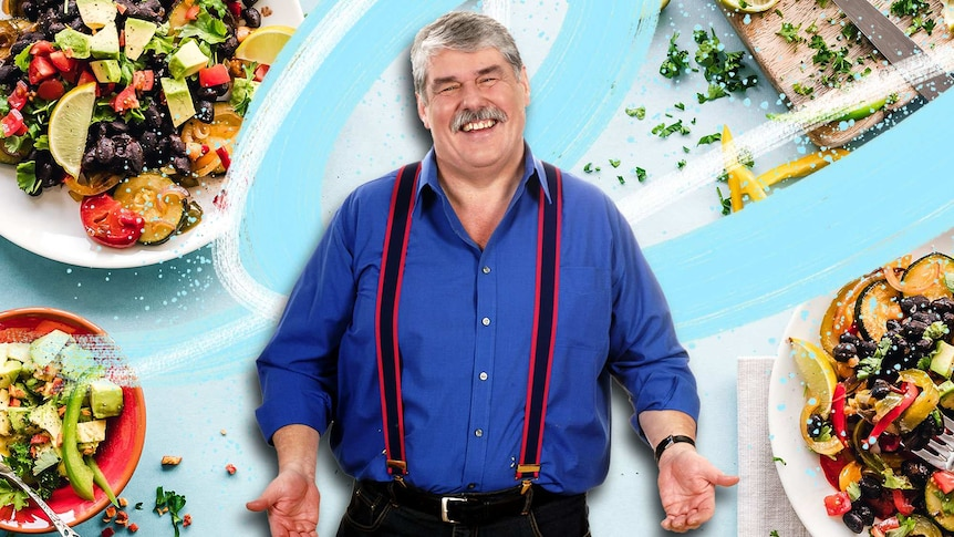 Chef Iain Hewitson in a portrait surrounded by plates of food, he advocates for keeping home cooking simple.