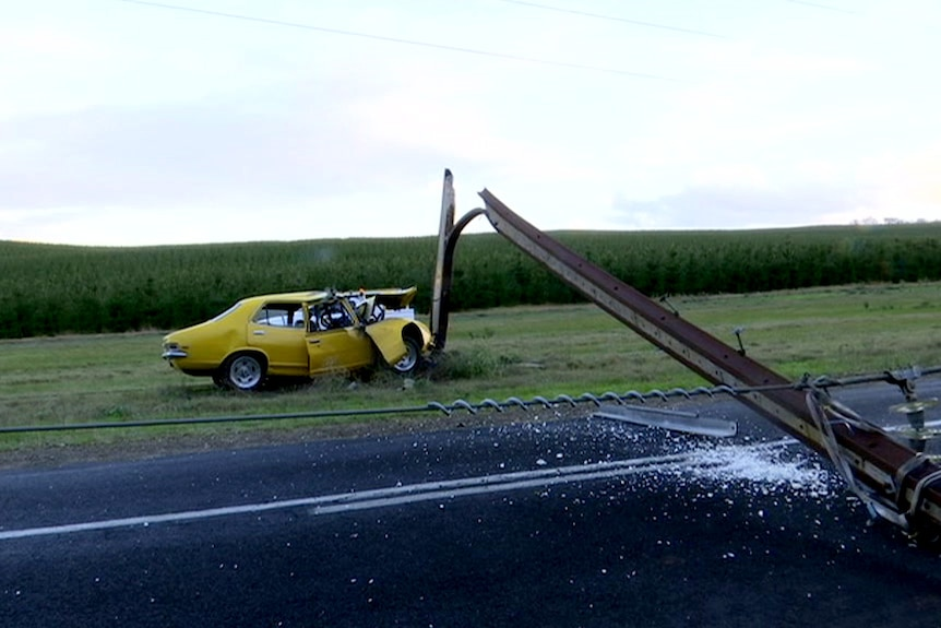 A car crumpled against a power pole which has split and fallen.