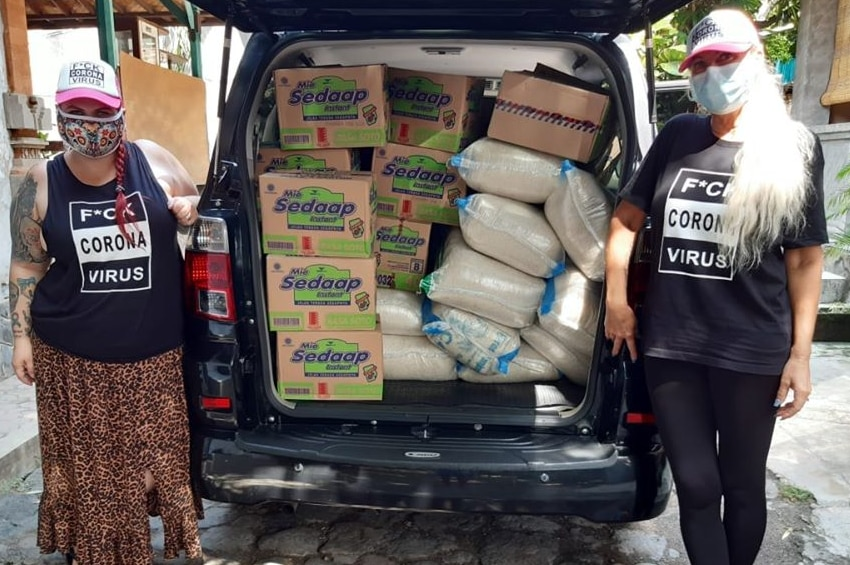 Two Australian women wearing a mask next to a car filled with boxes of instant noodles and rice.