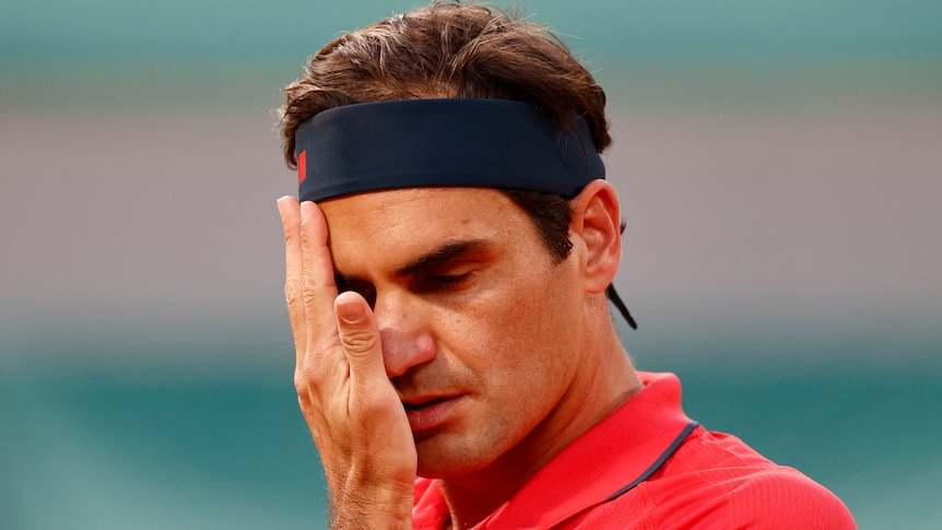 A Swiss male tennis players wipes his face with his right hand at the French Open.