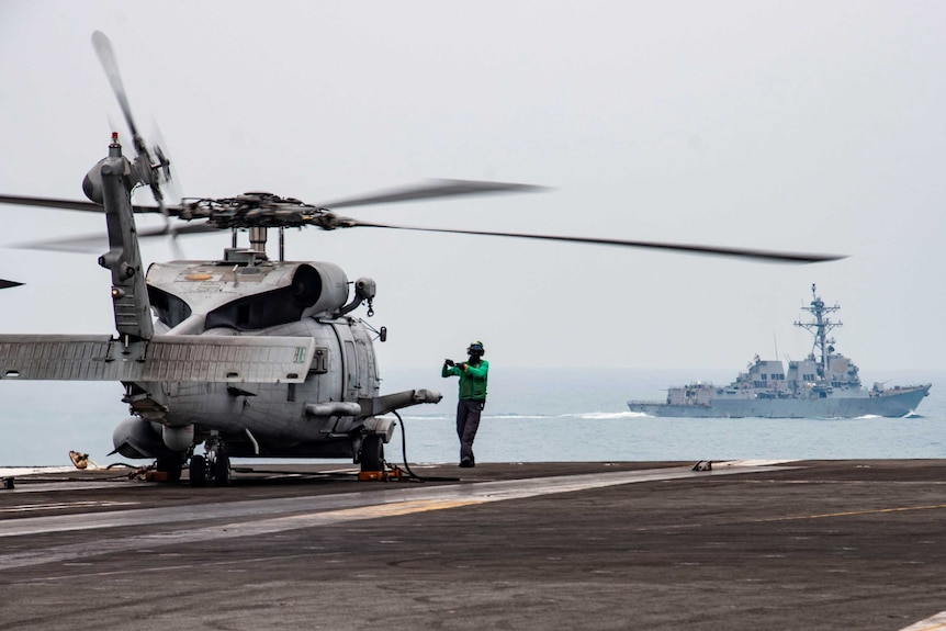 A man in green stands in front of a helicopter on an aircraft carrier with a naval ship in distance.