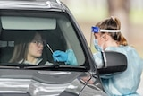 A medical worker takes a sample from a person at a drive-through COVID-19 pop-up testing clinic
