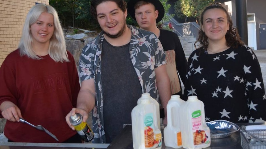 Four people smiling to the camera as they cook at a barbecue
