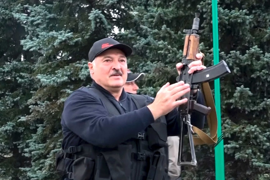 Lukashenko holds up  a rifle.