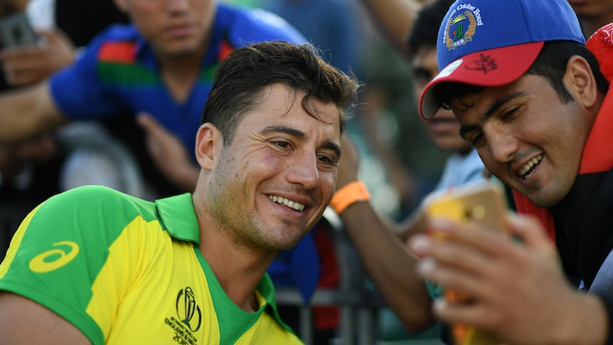 Marcus Stoinis smiles while leaning towards a fan wearing an Afghanistan Cricket Board cap, who is holding a phone