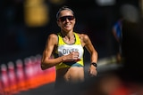 Sinead Diver smiles as she runs, wearing sunglasses