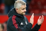 Ole Gunnar Solskjaer applauds the crowd while wearing a frown