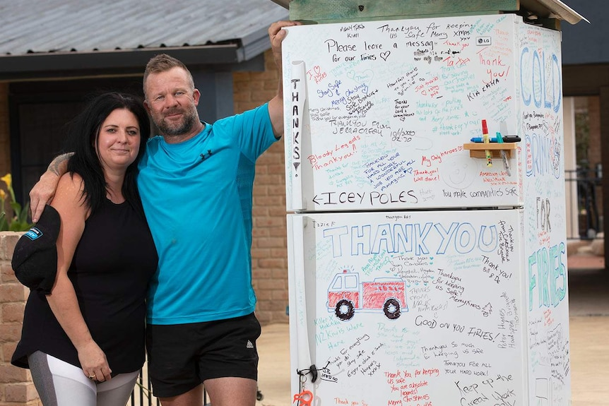 a man and woman next to a fridge with thank messages scribbled across it