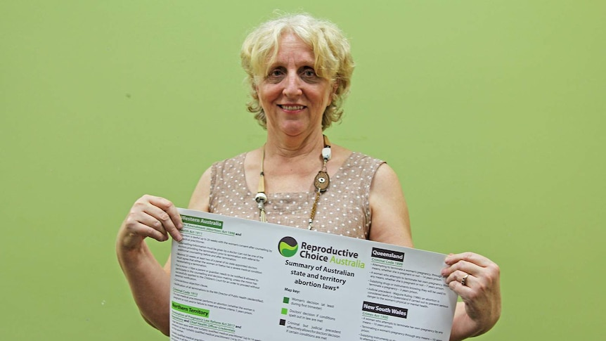 Women's reproductive right campaigner Robyn Wardle proudly holding a sign that maps out abortion laws in Australia.